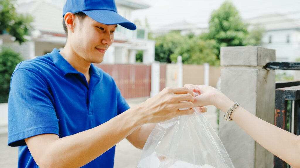Asia postal delivery courier man in blue shirt handling food boxes for sending to customer